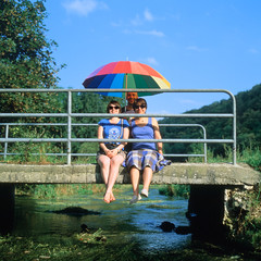 Bridge Over Troubled Water (christian.senger) Tags: bridge family blue portrait sky woman man green 6x6 film water rollei analog rolleiflex umbrella mediumformat river germany geotagged outdoors europe fuji velvia squareformat wife sl66 handrail lightroom vuescan colorperfect gettygermanyq4 christian_senger:year=2012