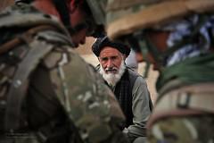 Patrol of Soldiers Files Past Afghan