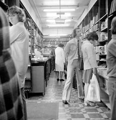 Spotted in the book shop (Tyne & Wear Archives & Museums) Tags: world city shadow portrait people blackandwhite woman man shirt standing shopping newcastle tile screw carpet shoe lights book back interesting globe community pattern highheel photographer dress floor trolley candid coat tie books demolition ceiling shelf mat cover photograph plasticbag intriguing trousers worker unusual everyday 1970s shoulder bookshop crease bookcases westend attentive shoppers flares newcastleupontyne digitalimage artificiallight generalpublic wavyhair socialhistory graingermarket menandwomen housingestates early1970s rolleiflexcamera workingenvironment bankloan directeyecontact newcastlescenes roberthopecollection