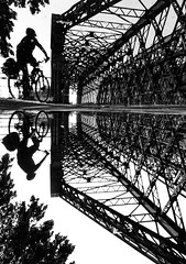 paper cut biker pt.2 (- Georg K -) Tags: street bridge urban bw white black reflection bike bicycle silhouette architecture contrast paper puddle mono mirror dresden industrial cut geometry helmet streetphotography brain structure biker protector