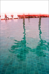 heat - hua hin (chirgy) Tags: orange white distortion pool lines palms thailand turquoise cyan plastic burn tiles heat huahin olympustrip35 relfection 1032 5f sunchairs duochrome autaut 5f48 reflections2012