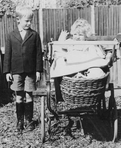 boy plant grass leaves fence garden kid child basket jacket shorts wellies blazer pram