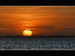 Sunset at the Oosterschelde (Wim Koopman) Tags: blue sunset sea orange sun holland reflection netherlands yellow river photography gold coast photo nikon magic stock nederland delta zeeland hour stockphoto stockphotography d90 estuarium wpk