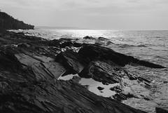 Lakeshore Layers (Reptilian_Sandwich) Tags: statepark trees sky blackandwhite bw water pool walking sandstone waves hiking michigan interface shoreline highcontrast spray shore foam lakesuperior stopmotion afternoonlight sedimentaryrock stratification lakeshoretrail porcupinemountainswilderness