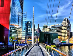 Baltimore Cityscape (` Toshio ') Tags: city bridge blue sky people woman man reflection building window water glass architecture clouds buildings harbor downtown cityscape fuji perspective maryland baltimore tourists ripples hdr highdynamicrange innerharbor nationalaquarium toshio x100 flickrstruereflection1