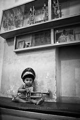 Li'l Miss Trumpet (Satyaki Basu) Tags: street portrait people india girl hat shop canon eos kid child indian central band trumpet organ 1750 tamron brass kolkata bengal bnw calcutta westbengal 450d gettyimagesmiddleeast