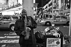 Fashion's Night Out (sjmgarnier) Tags: 2011 bw bwstreetphotography cabs evening fashionsnightout man manhattan music musician nyc newyork newyorkcity night people playingmusic saxophon saxophonist september sidewalk street streetart streetartist taxis timessquare trash trashcan usa urban