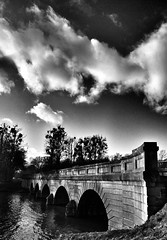 Bridge at Virginia Water, Surrey (King Grecko) Tags: park lighting uk bridge trees shadow england blackandwhite bw cloud black tree history tourism water silhouette contrast canon vintage pattern moody arch darkness patterns wide perspective sigma wideangle arches surrey shade 7d atmospheric virginiawater ipad sigma1020 flickraward canon7d snapseed
