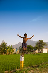 J.O.Y | B.O.Y (VinothChandar) Tags: blue boy portrait sky india playing color colour green grass stone kids rural children happy freedom kid jump jumping colorful village play emotion expression vibrant joy vivid happiness enjoy edge balance colourful joyful grassland tamilnadu tiruvannamalai ontheedge thiruvannamalai
