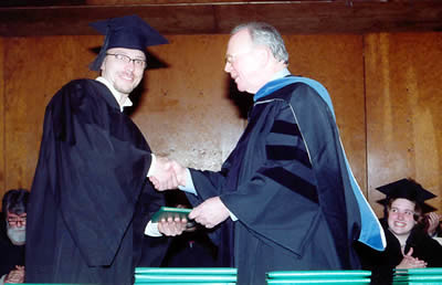 Aaron Kisicki Shakes Hands with Andy Hilton, Chair of the Board of Trustees
