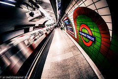 The Dark Blue Line of Busyness (Aaron Yeoman [Old Account]) Tags: city uk greatbritain travel blue light red england people urban motion blur green london lines station architecture speed underground subway tile movement europe metro unitedkingdom sony curves perspective platform railway blurred line fisheye tiles gb tubestation subwaystation alpha curve vignetting vignette hdr highdynamicrange metrostation piccadillyline tfl undergroundstation rapidtransit piccadillycircusundergroundstation a700 fluorescentlamp metropolitanrailway fluorescentlamps sonyalpha700 dslra700 piccadillycircustubestation samyang8mmf35mcfisheye