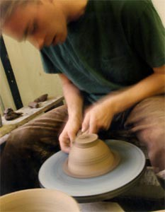 A Student at the Wheel in the Pottery Studio.