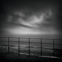 Severance (Andy Brown (mrbuk1)) Tags: longexposure sky cloud seascape wet lines fence reflections dark square mono blackwhite moody pavement grain platform dramatic plymouth eerie crack burn devon dodge split posts filters toned railings vignette atmospheric wispy neutraldensity