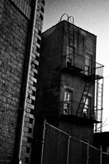 Old and Stark (EcstaticAperture) Tags: old blackandwhite bw streets architecture contrast balcony grain grainy stark longislandcity noisy fireescapes seedy blownhighlights nosie escapeladders