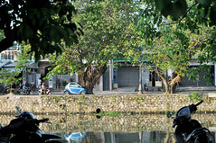 Along the river (Roving I) Tags: trees houses homes water reflections transport vietnam vehicles rivers stonewalls hue compacts europeancars motorscooters