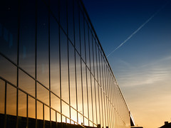 Segments (Rutger Blom) Tags: blue light sky sun reflection building window glass lines yellow facade airplane contrail afternoon sweden malm reflexion vapourtrail reflectie spegelbild entr canonpowershots100 5226mm