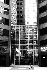 JFK Boulevard, Philadelphia (lucymagoo_images) Tags: street city urban bw woman building tower philadelphia monochrome lines walking alone squares geometry towers pedestrian sidewalk single philly solitary jfkboulevard towered lucymagoo lucymagooimages