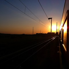 train sunset (SS) Tags: light sunset shadow red italy orange brown sun motion hot reflection lamp colors lines weather yellow composition contrast train buildings reflections landscape photography evening countryside moving focus colorful mood glow shadows dof view angle pov walk details year perspective scenic favorites gimp fast clear burning crop page rays spicy framing treno nero depth tone leading comments shimmer lazio lampione iphone riflesso pendolare shimmers atmophere
