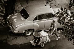 Walking Past an Olds (Erik Pronske) Tags: blackandwhite man car trash vintage walking havana cuba streetphotography cart 88 olds oldsmobile vedado