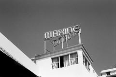 Maxine Hotel Scaffold Sign (Phillip Pessar) Tags: camera bw white black film beach sign analog 35mm hotel store florida zoom kodak miami infinity tx south trix olympus x thrift 400 scaffold tri 70 maxine sobe