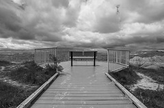 Conata Basin Overlook (s.d.sea) Tags: park trip travel vacation sky blackandwhite white black west monochrome clouds bench landscape outdoors spring midwest rocks mood moody pentax south perspective hills national badlands prairie dakota