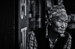 Looking out of the frame (Axel Halbgebauer) Tags: street old nepal portrait people blackandwhite man face look hat composition zeiss dark prime blackwhite lowlight asia sitting sony streetphotography oldman kathmandu wrinkles topi southasia saarc sonyalpha streetportait sonnar13518za sonyimages sonya7r2