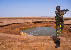 An ethiopian soldier in front of an acid lake in the danakil depression, Afar region, Dallol, Ethiopia (Eric Lafforgue) Tags: africa travel orange lake man color male nature horizontal danger soldier army outdoors spring gun day desert military acid border rifle guard salt security heat minerals copyspace ethiopia region volcanic geothermal arid oneperson hotsprings hornofafrica afar eastafrica abyssinia onlymen fulllenght onemanonly 1people afarregion dallol danakildepression oneadultonly ethio162082