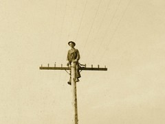 Man on Pole (Detail) (Alan Mays) Tags: ephemera postcards realphotopostcards rppc photos photographs foundphotos portraits men clothes clothing hats telephonepoles utilitypoles poles wires lines insulators farms fields fences heights danger dangerous precarious perspective vanishingpoint vanishingpoints distant distance receding strange unusual antique old vintage switzer awswitzer awswitzersphoto photographers studios vptp