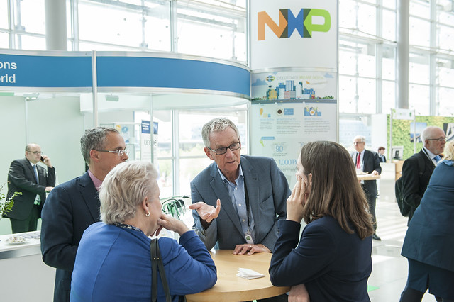 Attendees in discussion in front of the NXP stand
