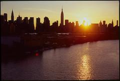 (Vitaliy P.) Tags: new york city nyc light sunset sun reflection building film water silhouette analog 35mm river 50mm nikon state manhattan f14 slide scan iso explore velvia empire epson gothamist 100 v600 fm10 setting explored vitaliyp