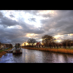 A change in the weather is sufficient to recreate the world and ourselves. Marcel Proust (genevieve van doren) Tags: trees houses sky mill grass landscape moulin boat canal maisons dramatic ciel arbres bateau paysage chanel hdr roseaux damme tourment