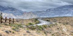 Redrock Loop Road (magnetic_red) Tags: road snow storm mountains color rain clouds fence landscape wooden nevada scenic stormy winding curve americanwest curvey