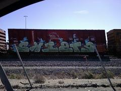 SKISTE (QsySue) Tags: railroad train graffiti tag traintracks freeway traincar takenwhiledriving cellphonepic railroadtracks cellphonecamera railroadcar inlandempire 10freeway sanbernardinocounty endtoend e2e skiste lotuslgcellphone