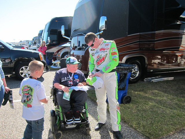 Dale Jr signing showing off his hat to a NASCAR Dreams child