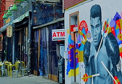 Ali's Alley (MPnormaleye) Tags: brick wall brooklyn bar painting table store mural fighter chairs streetlamp neighborhood ali business utata 24mm boxing