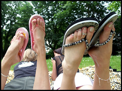 Zoe and Lessien's feet in flip flops (sunnystreets) Tags: street city feet female outdoors foot shoes toes sandals polish jewellery jeans rings nails flip barefoot flops pedicure soles anklets