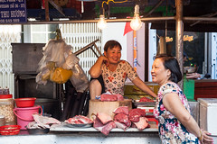 Two women are having a conversation at the wet market (Evgeny Ermakov) Tags: life street city people urban food woman smile smiling shop asian lights women asia southeastasia raw vietnamese emotion market sale traditional culture stall scene fresh meat vietnam business butcher exotic chi trading lanterns pavilion vendor marketplace local lantern ho southeast emotional typical sell trade selling minh saigon hochiminhcity seller salesman streetmarket hochiminh trader wetmarket editorialuse