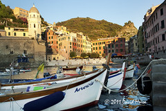 Vernazza By Day (David Morse) Tags: ocean street door wood old city blue trees light red sea sky italy orange brown sun white house black building tree green tower beach window water glass grass yellow pinetree pine canon geotagged 350d xt gold grey lights bay boat nationalpark pond sand sandstone rocks europe surf glow sad purple liguria gray ruin wave hills roofs canon350d cinqueterre rebelxt vernazza travertine morse graduatestudent canondigitalrebelxt 2011 davidmorse absolutelystunningscapes