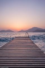Sunset pier (aleksey_kondratiev) Tags: turkey fethiye oludeniz mediterranean sea water blue wave waves seashore rocks sky sunset pier mountain