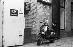 Parked. (greyo11) Tags: bike motorbike motorcycle cycle firedoor fire door street streetphotography moped scooter brick bricks architecture ilford hp5 nikon nikonf3 blackwhite blackandwhite bw wales uk cardiff britain british contrast monochrome mono 35mm 35mmfilm film ilfordhp5