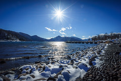 Lake Chzenji (ErikFromCanada) Tags: travel blue winter light sun mountain lake snow mountains cold water rock japan stone japanese coast cool dock rocks waves afternoon waterfront view angle bright stones wide rocky wideangle ridge nikko ultrawide beams snowcovered sunstar a7r chzenji lakechzenji