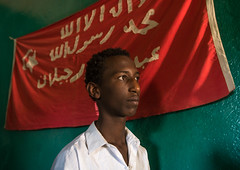 Sufi man worshipper in front of islamic red flag, Harari region, Harar, Ethiopia (Eric Lafforgue) Tags: africa travel red portrait people man color horizontal outdoors photography day adult african flag muslim islam faith religion indoor unescoworldheritagesite unesco indoors teenager spirituality ethiopia sufi sufism worshipper oneperson hornofafrica ethiopian harrar eastafrica placeofworship harar abyssinia arabiccalligraphy traditionalclothing harari oromo onemanonly waistup 1people harer harariregion hararjugol harergeprovince harergey ethio162911