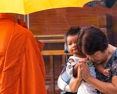Too young to pray (edwindejongh) Tags: street people yellow lady umbrella asian asia cambodge cambodia child looking pray picture monk buddhism kind gelb interested womanandchild geschenken monnik religie interessant boeddhisme bidden devoot straatfoto geinteresseerd cambodien gevouwenhanden gelovig verwonderd aanbidden geleparaplu kindopdearm