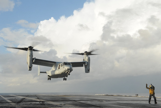 A Sailor signals an Osprey to land on the flight deck.