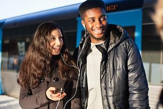Glada vänner på perrong med tåg lyssnar på musik i hörlurar