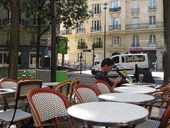 FIRST CUSTOMERS (RubyGoes) Tags: morning trees paris france glass restaurant cafe apartments crossing chairs drink pedestrian bicycles tables yamaha balconies pram jacadi abigfave chezginette ruedecaulaincourt