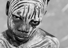 Portrait Of Young  Mursi Boy in Mago Park, Ethiopia (Eric Lafforgue) Tags: africa portrait people horizontal closeup artistic picture tribal ornament photograph blackpeople warrior omovalley bodypainting ethiopia tribe rite frontview adornment pigments nomadic eastafrica onepersononly humanface lookingatcamera 3400 childrenonly oneboyonly mursitribe indigenousculture 1011years 1213years snnpr southernethiopia nomadicpeople onechildonly toughlook truepeople exterioroutdoors omotic southernnationsnationalitiesandpeoplesregion blackethnicity peoplesoftheomovalley bodypaintingnaturalpatterndesignritualbodyart whitepaintchalkpatternsdesignbodypaintingritualpow ethiopianomovalley abyssiniahornofafrica blackandwhitephotoblackwhitepicturebw mursimurzu lfgethio3400