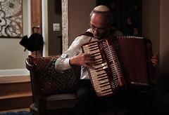 (CineWolf) Tags: light red musician music contrast lowlight shiny low oldman indoor scene story instrument accordian kippa