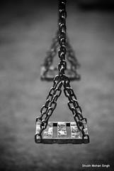 Swings (Shubh M Singh) Tags: india white black blur game monochrome kids triangles grey chains rust moody dof play swings ground swing simplicity weathered minimalism punjab grays