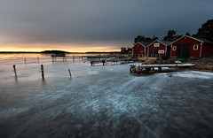 Frozen harbour (- David Olsson -) Tags: morning winter lake cold ice port sunrise dark landscape dawn march early frozen nikon quiet cloudy sweden harbour empty jetty sigma nopeople calm huts poles ropes cracks 1020mm 1020 vnern 2012 dx hammar vrmland lakescape noboats jettys skoghall d5000 floatingpier davidolsson trumman 2exposuremanualblend ginordicmar12 trummafiskehamn